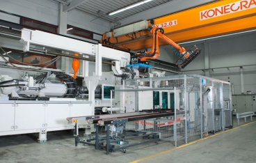 A robot loads and unloads injection molding machines at Krumpholz